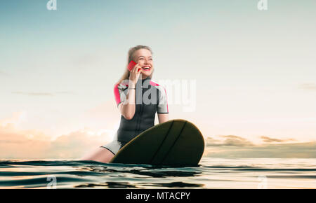 Female sportman windsurfer in wetsuit sitting on the board and talks by phone - Stock Photo