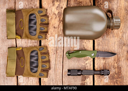 Military equipment and accessories. Flat lay, top view. Wooden desk surface background. - Stock Photo
