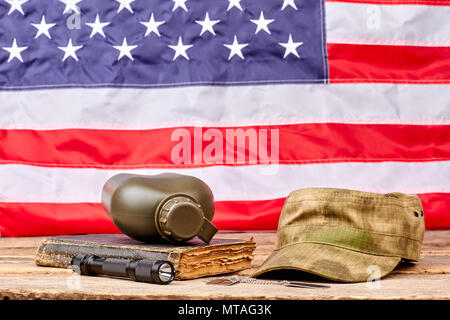 Military necessities in american flag background. Soldiers cap, bottle, book and torch. - Stock Photo