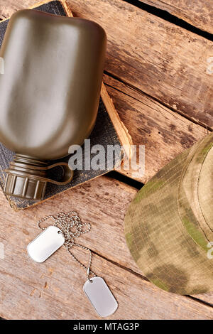Military essentials, top view. Green bottle, old book, dog tags and cap. - Stock Photo