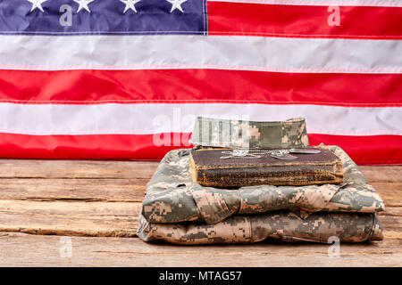 Folded army uniform with book and dog tags. American flag background. - Stock Photo