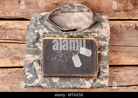 Camouflage army clothes, book, and dog tags on wood. Flay lay, top view. - Stock Photo