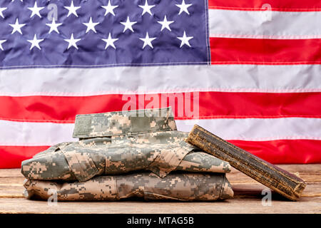 Soldier's diary and camouflage clothes. US flag background. - Stock Photo