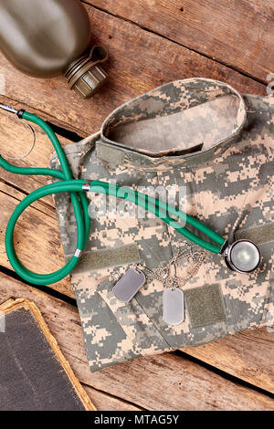 Soldier's outfit, equipment, and accessories. Camouflage clothes, stethoscope, bottle, diary and dog tags. - Stock Photo