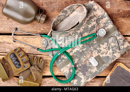 Medical soldier's essentials flat lay. Top view, stethoscope, clothes and accessories. Wooden background. - Stock Photo