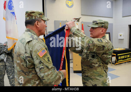 Maj. Gen. Troy D. Kok, commanding general of the U.S. Army Reserve's 99th Regional Support Command (right), and Command Sgt. Maj. Al Almeida, 99th RSC command sergeant major, affix the Army Superior Unit Award streamer to the 99th RSC Colors during a ceremony April 21 at the command's headquarters on Joint Base McGuire-Dix-Lakehurst, New Jersey. The 99th RSC received the award for providing aid and assistance from October 2012 to April 2013 to communities in New York City that were devastated by Superstorm Sandy. - Stock Photo