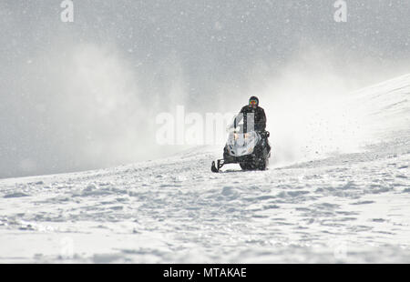 A man driving sports snowmobile in mountains - Stock Photo