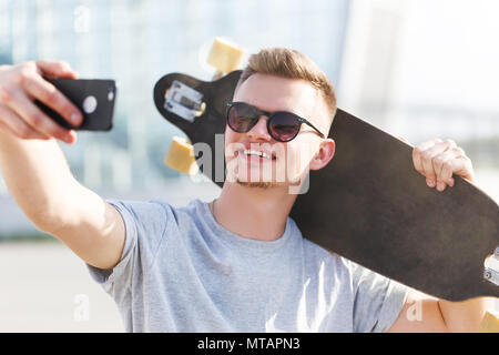 Skateboarder dressed in grey t-shirt and sunglasses making selfie on smartphone holding longboard on shoulder - Stock Photo