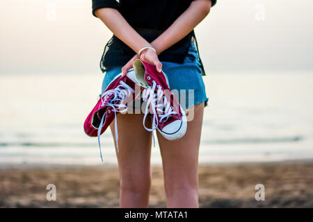 Girl walking towards water on the beach holding sneakers - Stock Photo