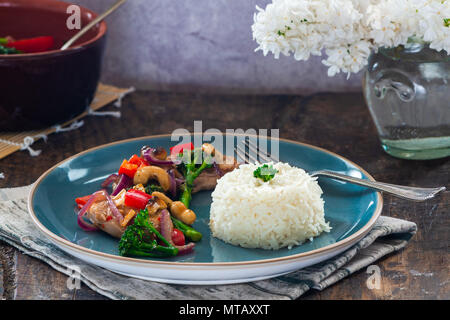 Sichuan pork, broccoli, red pepper and cashew stir-fry with rice - Stock Photo