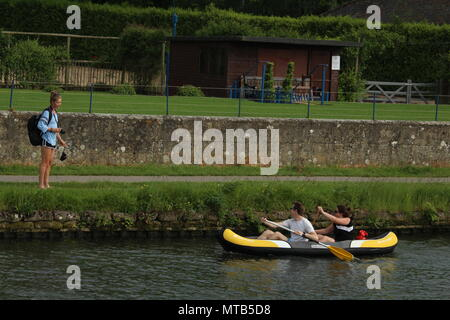 Lifestyle - young woman with blue top, black backpack and camera talking to a couple kayaking at Henley on Thames. - Stock Photo