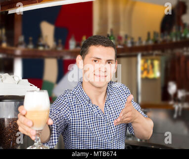 Handsome young smiling bartender serving a glass of tasty cockta - Stock Photo