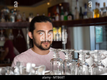 Portrait of handsome young smiling bartender behind the bar coun - Stock Photo