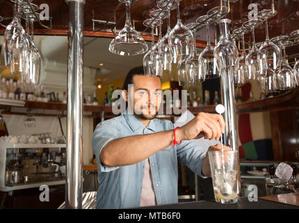 Handsome young smiling bartender holding steel swizzle spoon in  - Stock Photo