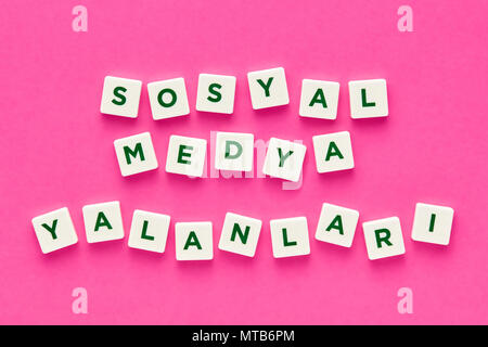 Social media lies words written in Turkish with green letters on white square buttons on pink background. Concept of social media deception and dishon - Stock Photo