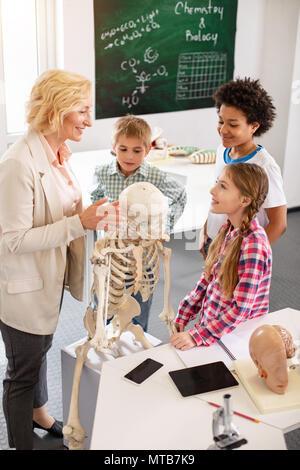 Joyful curious children listening to the teacher - Stock Photo