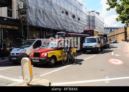 cyclist talks through a car window with taxi driver at a crossroads of London - Stock Photo