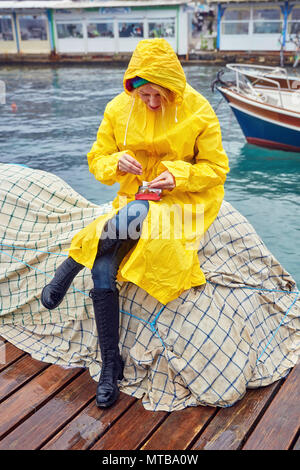 Caucasian woman wearing a yellow raincoat rolling a cigarette on the harbor on a rainy day. She is sitting on the fishing nets near the sea. - Stock Photo
