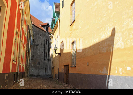 Hidden Old town street of Tallinn, Estonia. Sunny day, light and shadow. Walls of medieval buildings, Europe. - Stock Photo