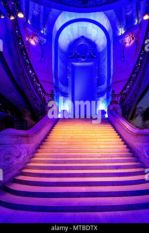 The grand staircase within the Grand Palais in Paris during an exhibit is lit with a blue and purple light. - Stock Photo