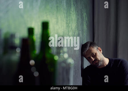 Man suffering from depression with empty alcohol bottles - Stock Photo