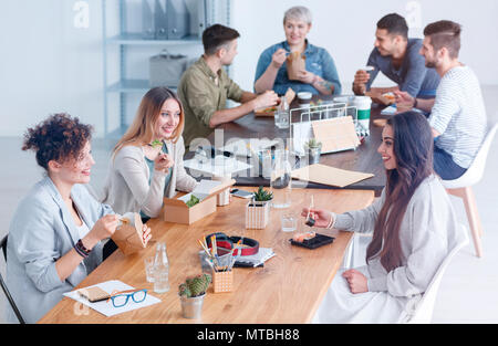 Colleagues chatting about a new concept in the office, during lunch break - Stock Photo