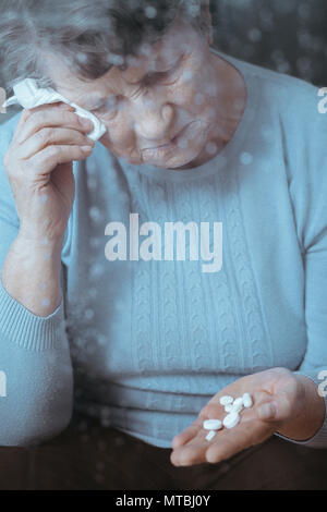 Ill senior woman crying, holding pills in hand - Stock Photo