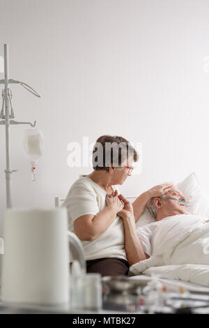 Elderly woman holding hand of sick dying husband in hospital - Stock Photo