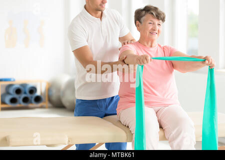 Elderly woman doing active pnf exercises with a teal scarf as a part of her rehabilitation program with a physiotherapist - Stock Photo