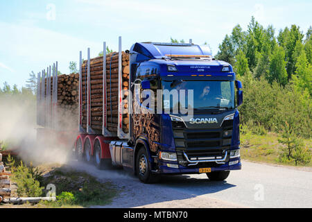Test drivers wave as they drive Next Generation Scania R730 logging truck on dusty rural road during Scania Tour 2018 in Lohja, Finland - May 25, 18. - Stock Photo