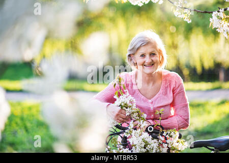 Beautiful senior woman with bicycle outside in spring nature. - Stock Photo
