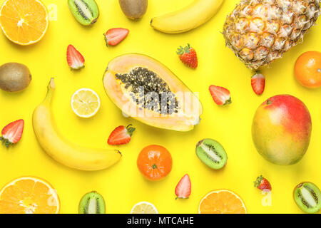 Ripe Organic Cut in Half Strawberries Kiwi Pineapple Mango Papaya Citrus Fruits Bananas Pattern on Yellow Background. Bright Sunny Colors. Flat Lay Ar - Stock Photo