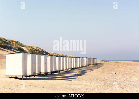 Row of white beach huts on an empty sunny beach in the province of Zeeland, the Netherlands - Stock Photo