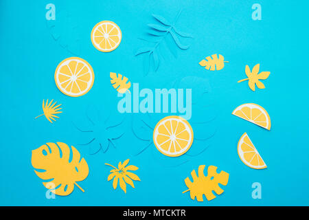Lemon slices and tropical leaves pattern on a bright blue background. Papercraft flat lay header. - Stock Photo