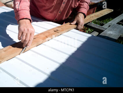A man with a flat Board draws a pencil line on a metal sheet. - Stock Photo