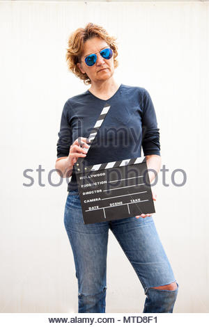 Cute woman holds a cinema slate in her hands - Stock Photo