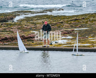 Milsey Bay, North Berwick. East Lothian, Scotland, United Kingdom, 30th May 2018.  A man having fun playing with radio controlled Kyosho Marine Racing sailing yachts in the tidal bathing pool with the sea and a wave breaking in the background - Stock Photo