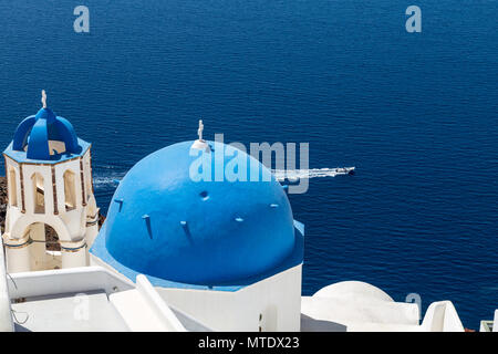 Motorboat driving past one of the blue domes of Oia, Santorini, Greece - Stock Photo
