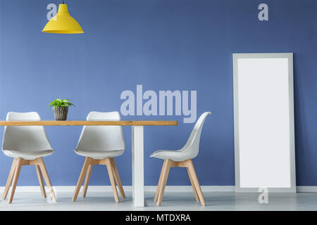 Modern open space interior with white and wooden chairs, table with a plant on top, yellow lamp and a mirror standing against blue wall - Stock Photo