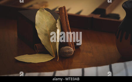 Cinnamon, nutmeg and bay leaves resting on a wooden table in a rustic setting - Stock Photo