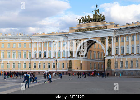 Saint-Petersburg, Russia - April 9, 2016: Ordinary people walk on Palace Square near General Staff Building - Stock Photo