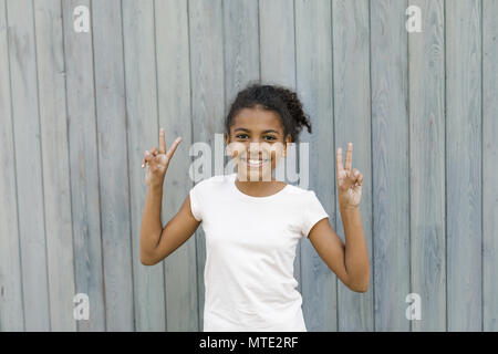 Cute girl showing victory sign, standing near a wall - Stock Photo