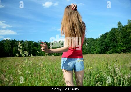 Young woman stands in green meadow surrounded by grass and wild flowers. Model holds her hand down, touches green grass. Photo without face. - Stock Photo