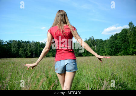 Young woman enjoys outdoor walk. Model in shorts walks along green meadow. - Stock Photo