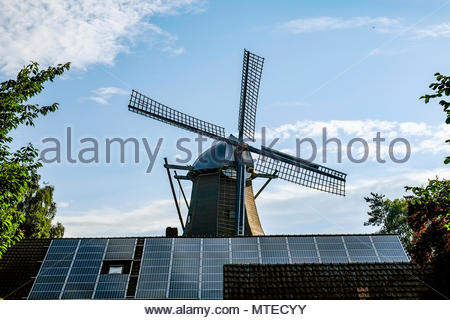 Traditional windmill juxtaposed with photovoltaic solar panels in Ramsloh, Saterland, Lower Saxony, northern Germany. - Stock Photo