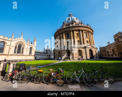 Bicycles on Railings Outside Radcliffe Camera, with all Souls College to the left, University of Oxford, Oxford, Oxfordshire, England, UK, GB. - Stock Photo