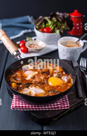 Shakshuka, Fried Eggs in Tomato Sauce for Easter Brunch. Top view. - Stock Photo