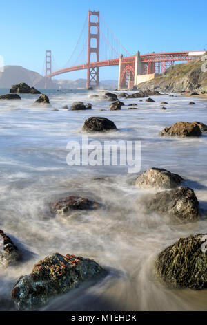 View of the Golden Gate Bridge from Rugged Marshall Beach in High Tide. - Stock Photo
