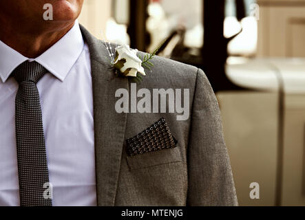 Smartly dressed man in a suit, shirt and tie with a white rose in his lapel at a wedding, could be the groom, father of the bride or best man. - Stock Photo