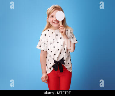 smiling modern child in red pants with covered one eye taking the visual acuity test against blue background - Stock Photo